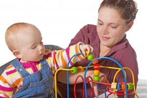 Baby with motor activity development delay being stimulated to develop muscle coordination and movement on a bead maze,